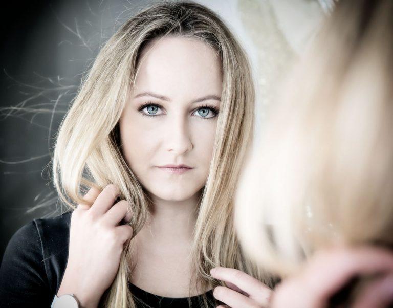 beauty fotoshooting mit biljana bili wechsler modell shooting die frau guckt direkt in die kamera lange blonde haare blaue augen laechelt