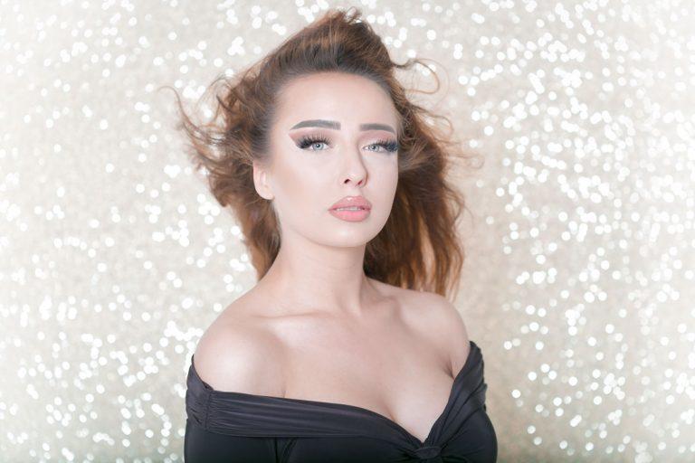 portrait beauty fotoshooting mit biljana bili wechsler modell shooting die frau guckt direkt in die kamera mit viel makeup lange braune haare blaue augen viel makeup