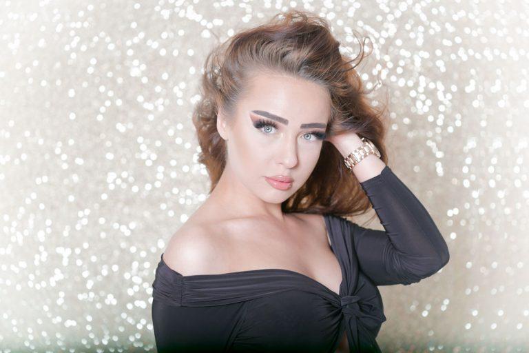 beauty fotoshooting mit biljana bili wechsler modell shooting die frau guckt direkt in die kamera mit viel makeup lange braune haare blaue augen